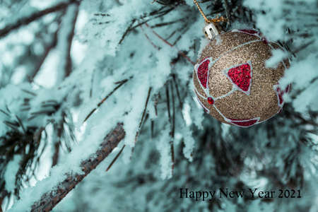Christmas ball on the background of a snowy fir tree. New year 2021