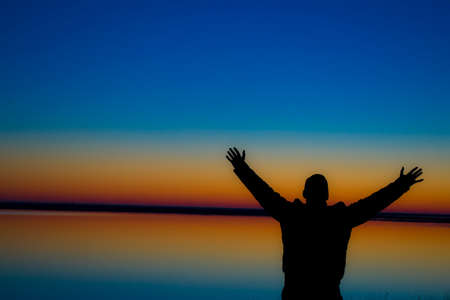 Silhouette of a guy with raised hands at sunset, the beginning of a new day and a new life. Stock Photo