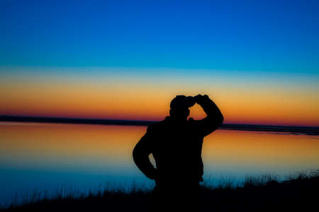 The silhouette of a guy at sunset, the beginning of a new day and a new life. Stock Photo