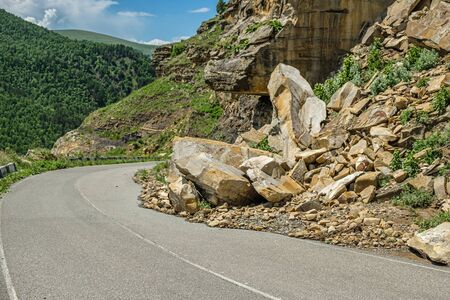 Rockfall on the road in the mountains. Stock Photo