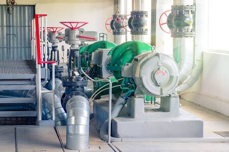 Several water electric pumps in the room of a thermal power plant.