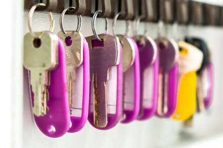 Keys with multi-colored tags hang in the wall box for storing the keys, close-up.