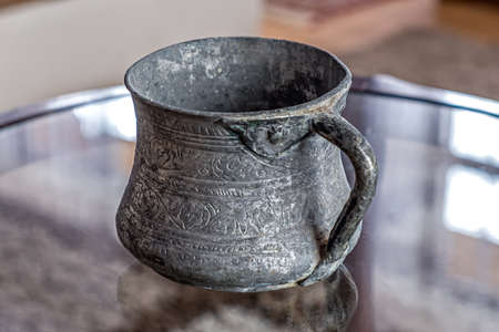 An ancient copper mug covered with tin, close-up. Stock Photo