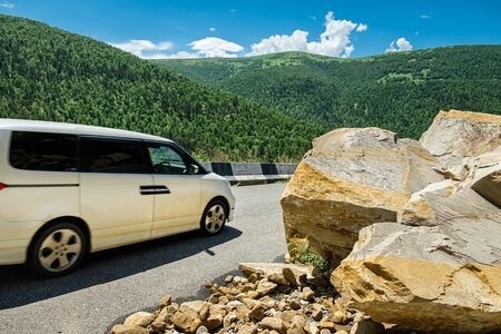 The car drives around the rockfall partially blocked the mountain road.