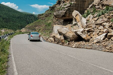 The car drives around the rockfall partially blocked the mountain road. Stock Photo