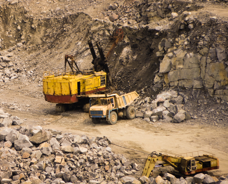 dump truck: excavator loading stone on a dump truck Stock Photo