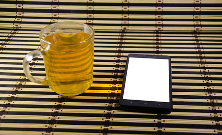 The cup of tea and smartphone on bamboo mat Stock Photo