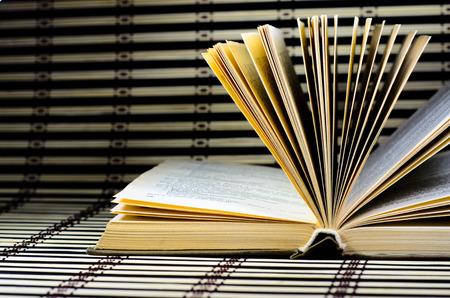 An open book on the bamboo mat Stock Photo