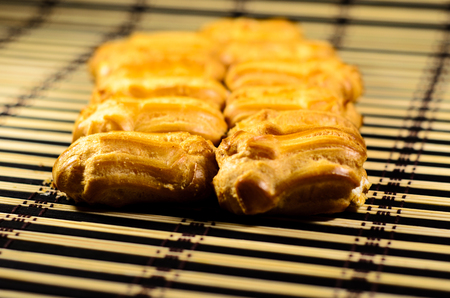 Rows of fresh eclairs on a bamboo mat. Selective focus