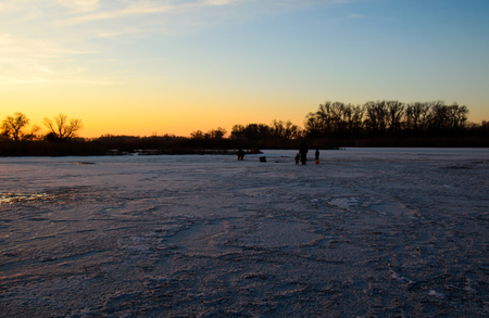 Winter fishing on a frozen river Dnieper at sunset
