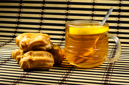 Tasty eclairs and cup of tea on a bamboo mat Stock Photo