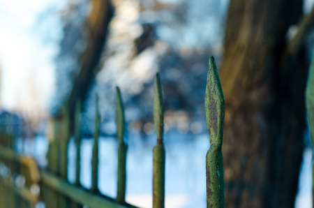 Old cast iron spiked fence in a city park