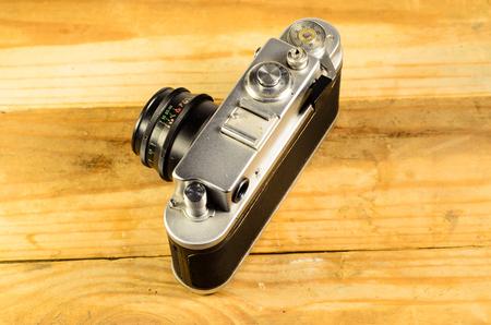 Old vintage soviet rangefinder camera on a wooden table