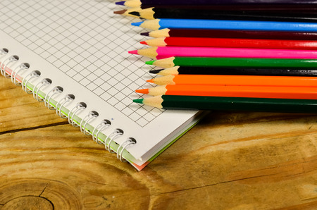 yellow notepad: Notebook with colour pencils on a wooden table