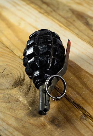 lanzamiento de bala: Black hand grenade on the wooden table