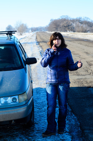 call for help: Young woman call for help and hitchhiking near the broken car on roadside Stock Photo