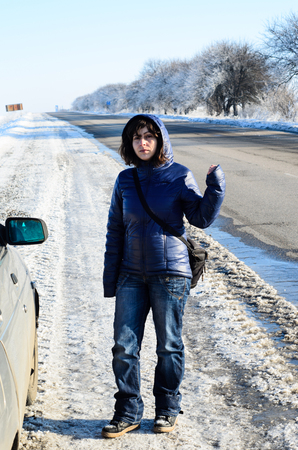 winter tires: Young woman hitchhiking on a roadside near the broken car