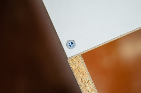 plywood: Close-up of the screw in the chipboard futniture. Woodworking and carpentry