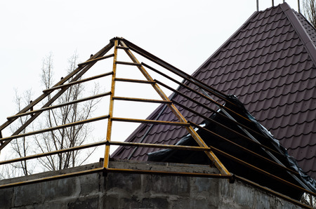 Roof construction with the logs and metal tile Stock Photo