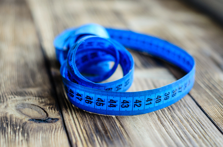wooden metre: Blue measuring tape on a wooden background