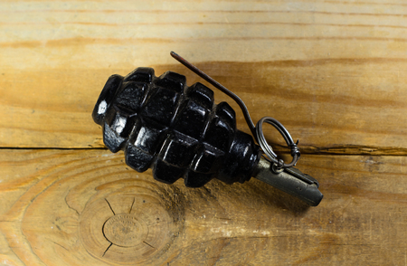 Black hand grenade on the wooden table