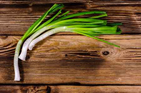 Fresh green onion on wooden table. Top view