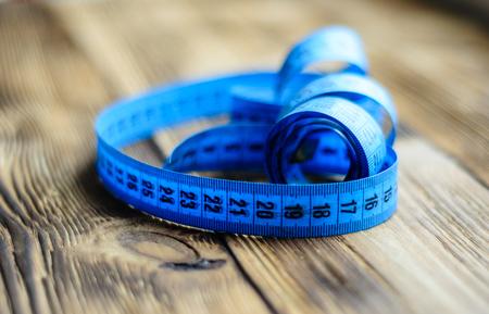 Blue measuring tape on a wooden background Reklamní fotografie - 76796914