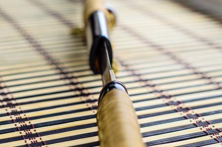 scabbard: Japanese sword katana on a bamboo mat. Selective focus