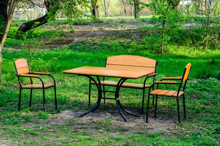 Houten tafel en stoelen op een groen gazon