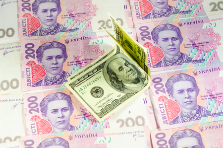 hryvna: One hundred dollars banknotes on the heap of ukrainian hryvnas