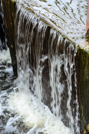 cascade: Water flowing from a dam on lake Stock Photo