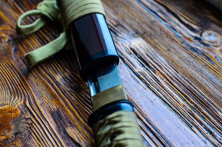 Japanese sword katana on a wooden background