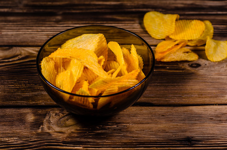 Potato chips in glass bowl on rustic wooden table Stock Photo