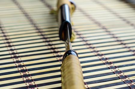 bushido: Japanese sword katana on a bamboo mat. Selective focus