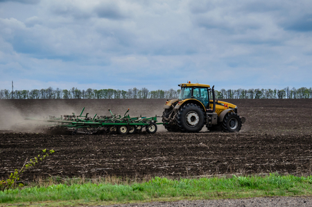 Tractor cultivating field on cloudy spring day Stock Photo