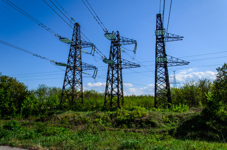 metal grid: High voltage power lines and towers against blue sky