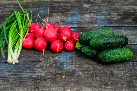 Radish cucumbers and green onion on rustic wooden table