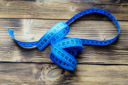 dimensions: Blue measuring tape on a wooden background