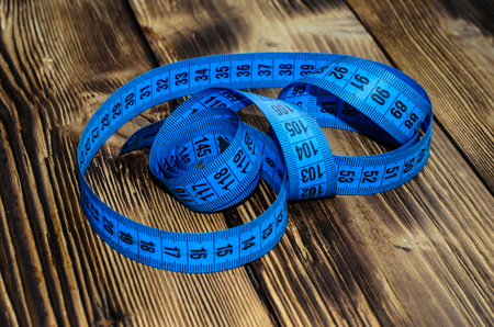 Blue measuring tape on a wooden background