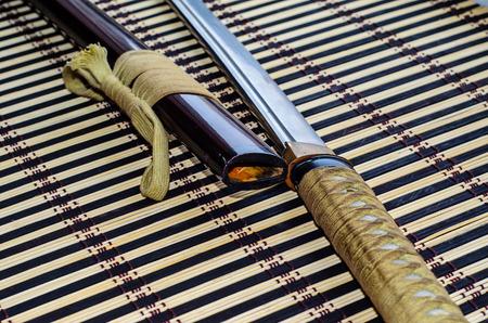 Japanese sword katana on a bamboo mat 写真素材