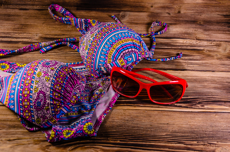 Swimsuit and sunglasses on rustic wooden background. Summer holiday concept