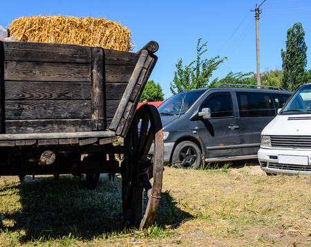 Old rustic cart in front of modern cars