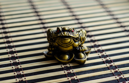 animal figurines: Chinese lucky toad on a bamboo mat