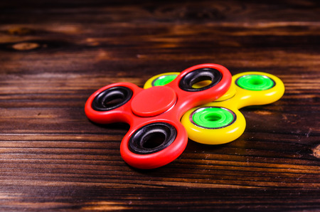 hype: Yellow and red fidget spinners on rustic wooden desk