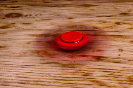 cool gadget: Red fidget spinner rotates on rustic wooden desk