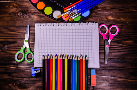 paper sheet: Set of different school stationeries. Notepad, scissors, pensils, paints, paintbrushes on rustic wooden desk. Back to school. Top view