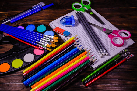 rubber sheet: Set of different school stationeries. Notepad, scissors, pensils, paints, paintbrushes on rustic wooden desk. Back to school