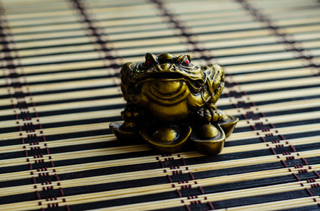 Chinese lucky toad on a bamboo mat