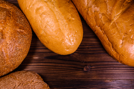 whole wheat toast: Different loafs of bread on rustic wooden table. Top view Stock Photo