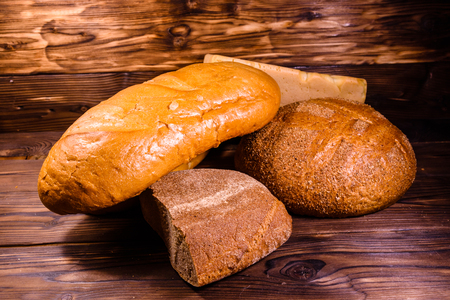 Different loafs of bread on rustic wooden table